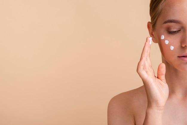 Donna del primo piano con crema per il viso e copia-spazio