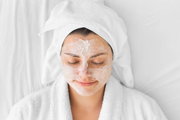 Donna del primo piano con crema per il viso