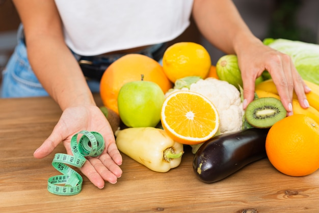 Close-up woman with fruits and measuring tape