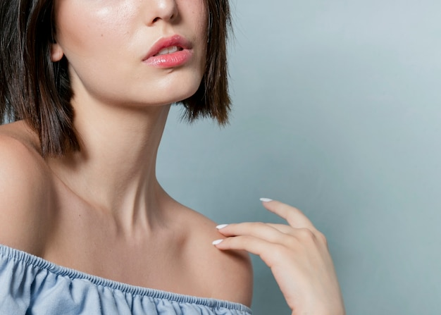 Close-up of woman with hand and ruffle top