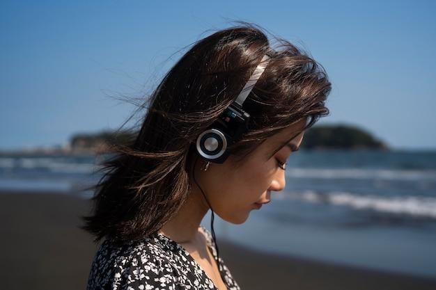 해변에서 헤드폰으로 여자를 닫습니다