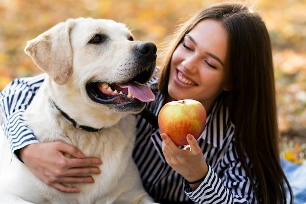 公園で彼女の子犬とクローズアップの女性