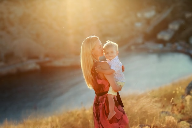 Close up of a woman with long blond hair outdoor with a baby boy in her arms