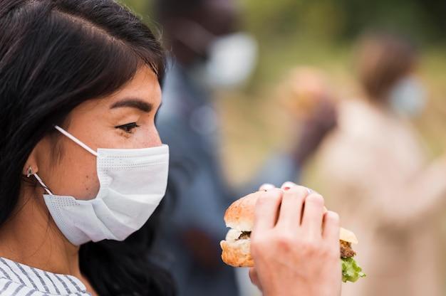 マスクとハンバーガーのクローズアップ女性