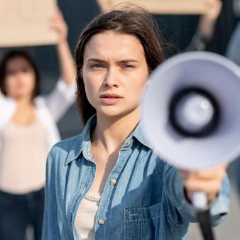 Макро женщина с мегафоном на демонстрации