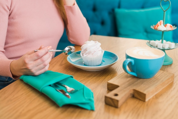 Close-up of a woman with meringue and coffee cup on wooden table