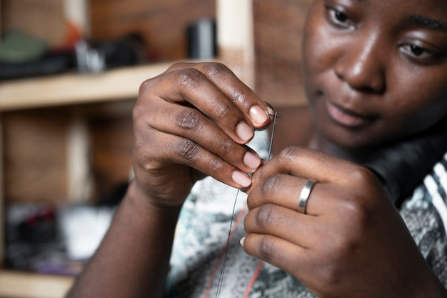Close-up woman with needle and thread