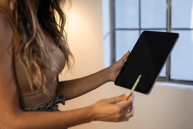 タブレットを保持しているペンで女性をクローズアップ