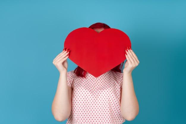 Крупным планом женщина с рыжими волосами прячет лицо за большим красным бумажным сердцем
