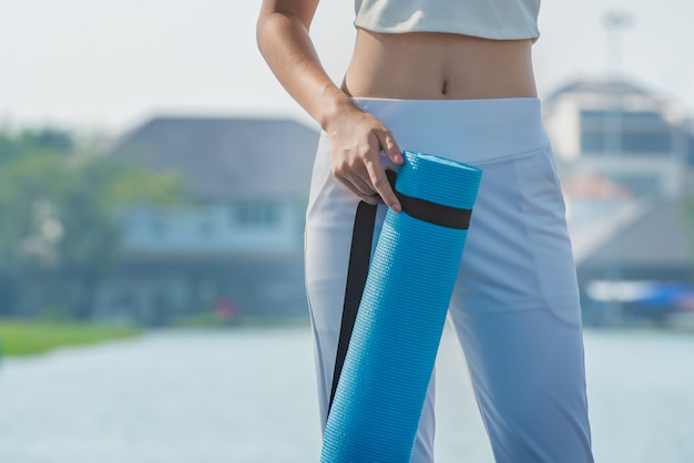 Close up of woman with slender body holding yoga mat.