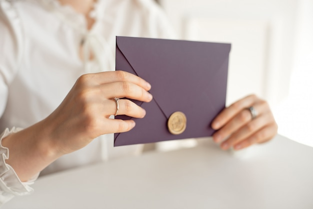 Close-up woman with slim body holding in hands the invitation card purple color square shape envelope card.