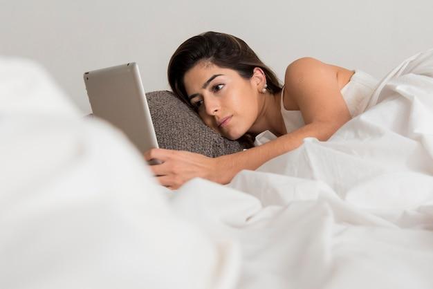 ベッドの中でタブレットを持つクローズアップ女性