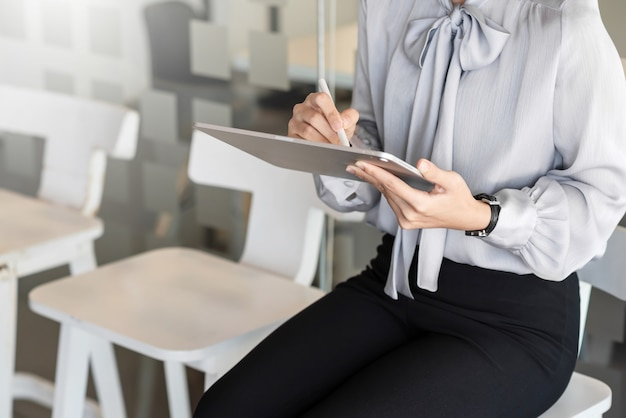 Close up of a woman with a tablet sitting in the office for a job interview.