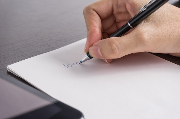 Close up of woman with tablet and write a paper