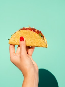Close-up woman with taco and green background