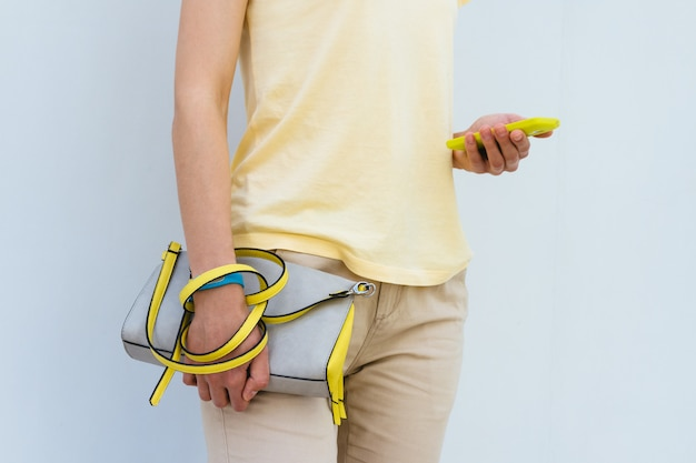 Close-up of a woman with a yellow mobile phone and female bag in hands outdoors