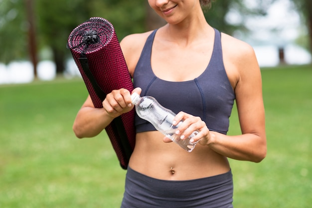 Close-up woman with yoga mat and water bottle