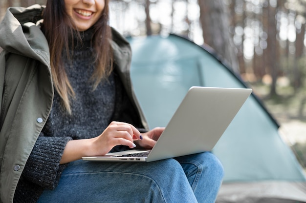 Chiuda sulla donna che lavora al computer portatile