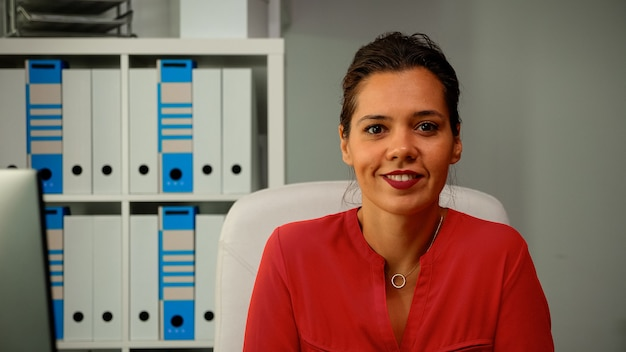 Close up of woman working and looking at camera. slow motion of hispanic freelancer sitting on chair and typing on computer in professional workplace in personal corporate company smiling at webcam