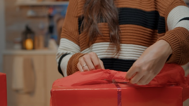 Close up of woman wrapping bow on gift for friends