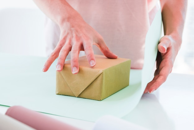 Close-up of woman wrapping the gift box with paper on table