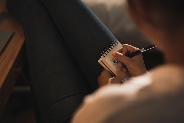 Макро женщина, пишущая в тетради