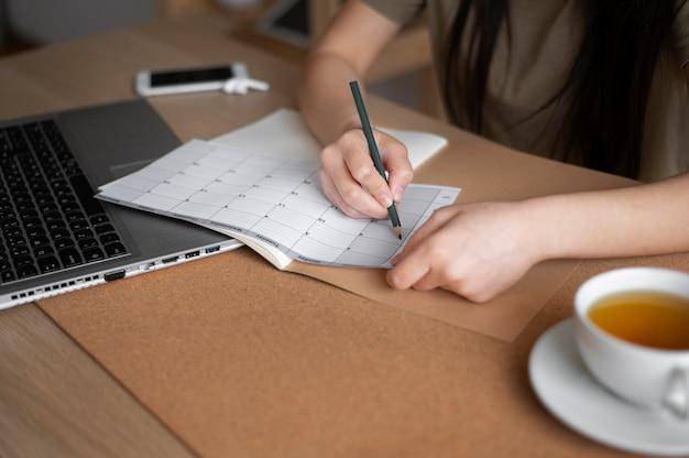 Крупным планом женщина, пишущая карандашом