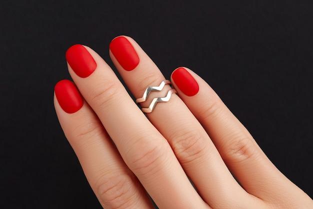 Крупным планом женская рука с красными матовыми ногтями на черном фоне тенденции дизайна педикюра маникюра