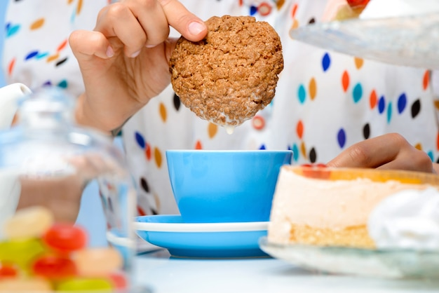 Close up of womans hands dipping cookie in milk