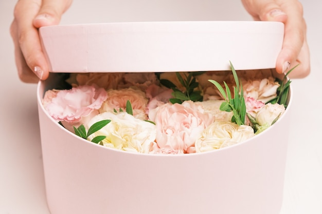 生花のギフトボックスを開く女性の手を閉じます。春が来ています、国際的な女性の