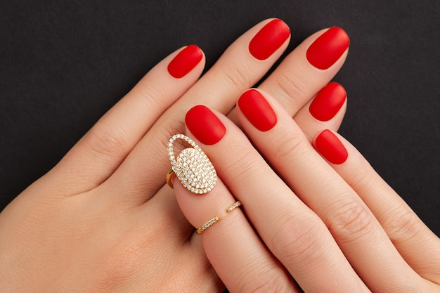 Close up womans hands with red matt nails on black background manicure pedicure design trends