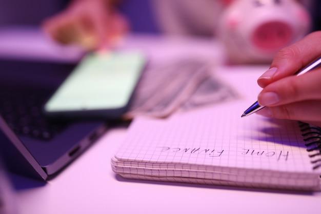 クローズアップ、女性の手がメモ帳の家計簿を書く