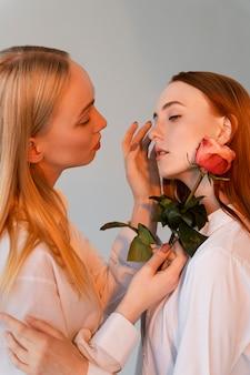Крупным планом женщины пара позирует с розой