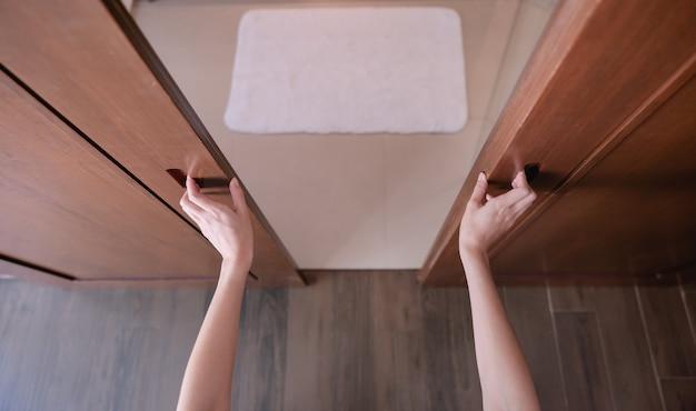 여자 손을 닫고 문 손잡이를 열거 나 나무 문을 누르십시오.