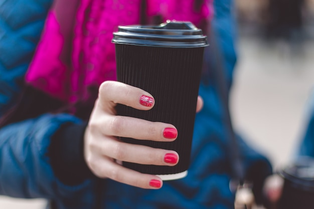 Close up of women hands holding paper cup of coffee