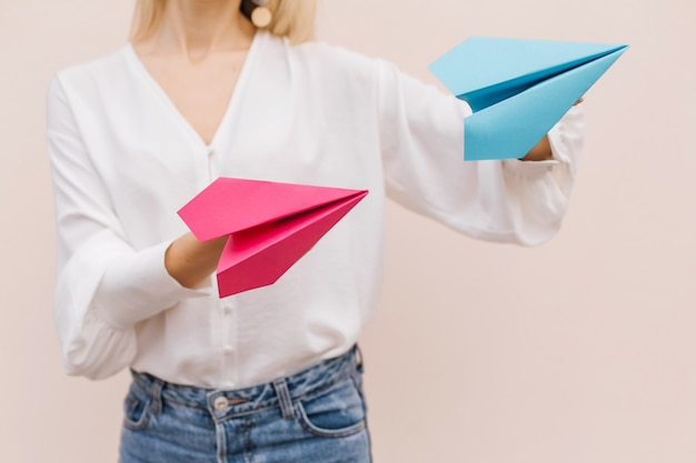 베이지 색 바탕에 분홍색과 파란색 종이 비행기를 들고 여자 손을 닫습니다.