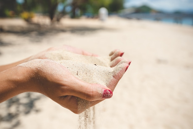 Close up women hands holding sand. summer beach holiday vacation concept