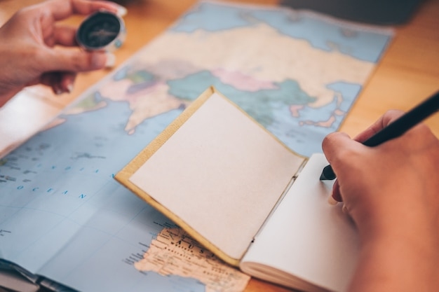 Close-up of women hands pointing at on world map on table