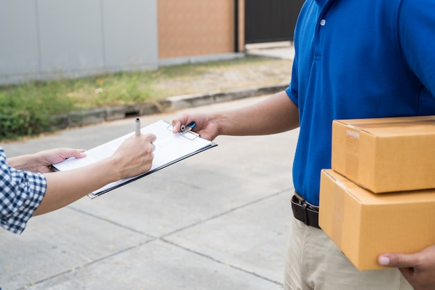 Close up women hands signing to get her package from delivery man.