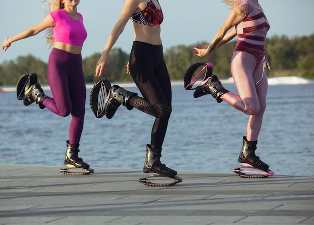 夏の晴れた日に通りでカンゴージャンプ靴でジャンプするスポーツウェアの女性をクローズアップ。高くジャンプする、アクティブな動き、アクション、フィットネス、ウェルネス。トレーニング中に女性モデルをフィットさせます。
