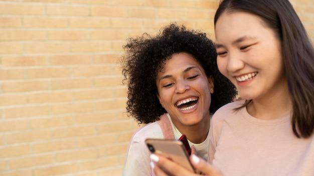Закройте вверх по женщинам, смотрящим на смартфон