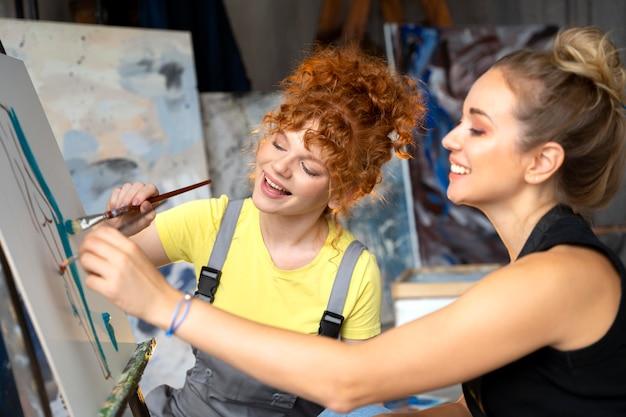 Donne ravvicinate che dipingono su tela