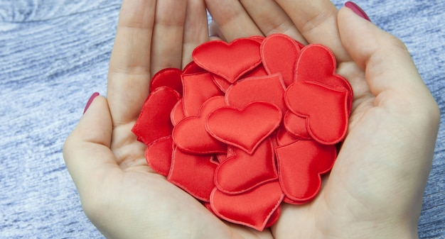 Close-up. women's hands hold many red hearts in the palm against the wooden background of jeans color, the concept of saving love