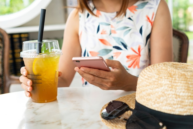 Close up of women's hands holding drinks while using mobile phone in cafe.