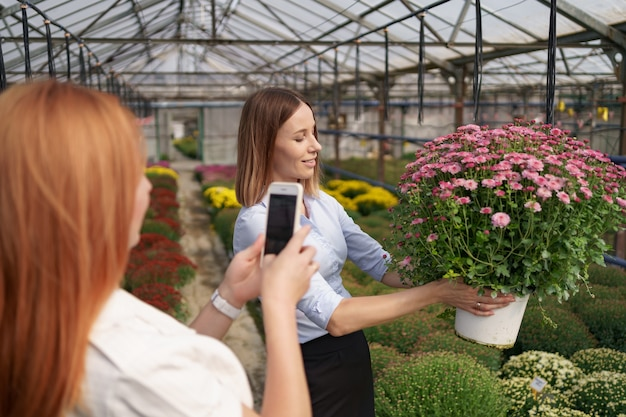 Close up women's hands holding phone and taking photo of girl with flowers.