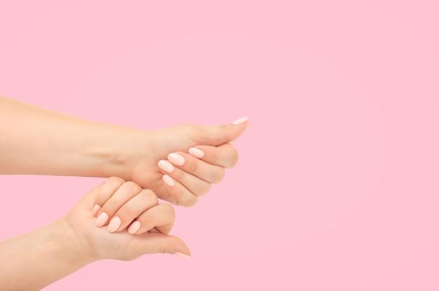 Крупным планом женские руки с красивым маникюром изолируют на розовом фоне. вид сверху. стильный модный ноготь молодой женщины руки розовый маникюр на розовом фоне. копировать пространство