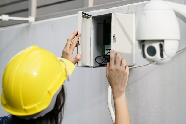 Close up of women technician fixing cctv camera on wall