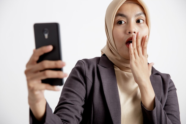 Крупным планом женщины в костюмах хиджаба удивлены, глядя на телефон, концепция формальной работы изолирована на белом фоне