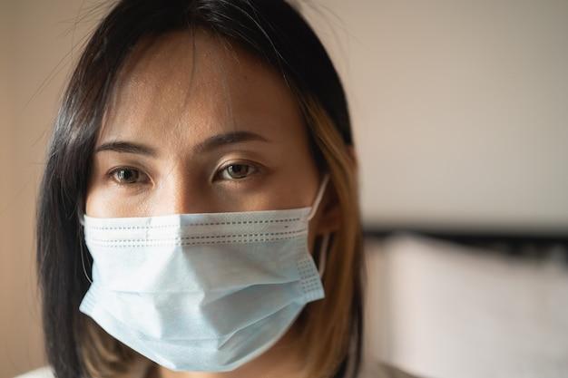 침실에서 수술 용 마스크를 착용하는 여성을 닫습니다.
