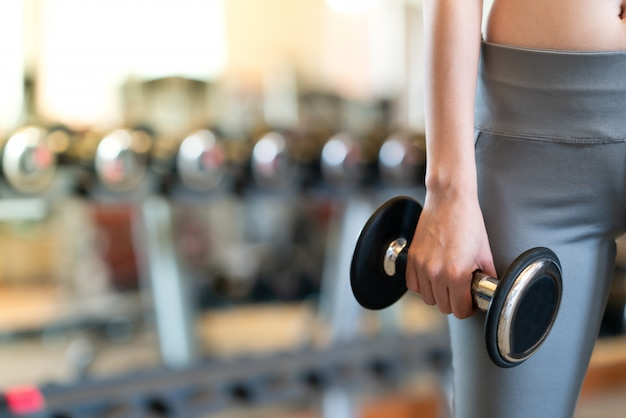 Close up women with dumbbells in hands the gym